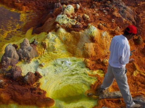 Small pond at the margin of a hydrothermal system depositing a variety of sulphates and iron oxides.